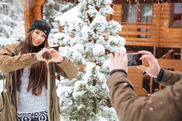 手で心を示し、スマートフォンで彼女の写真を撮る彼女のボーイフレンドにポーズをとってかわいい若い女性