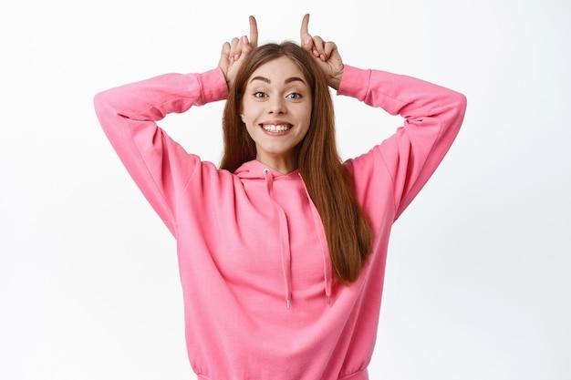頭に指で角を示し、正面で陽気な笑顔、白い壁の上に立っているかわいい若い女性