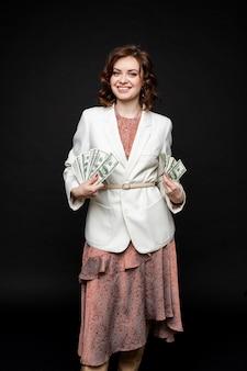 かわいい若い女性は手にたくさんのお金を示しています