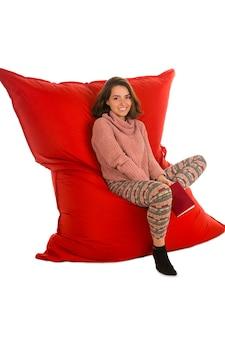 居間または他の部屋の赤いお手玉のソファの椅子に座って、白で隔離の本を保持しているかわいい若い女性