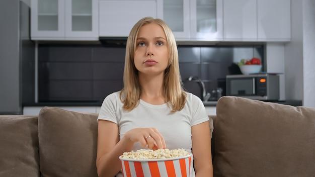 Милая молодая женщина сидит на диване и смотрит фильм с попкорном.