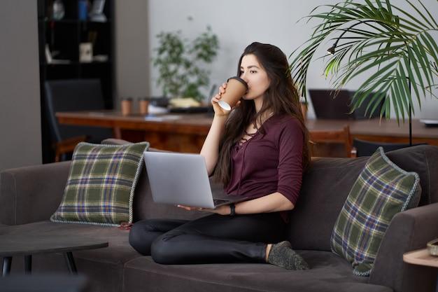 コーヒーとラップトップでソファに座っているかわいい若い女性