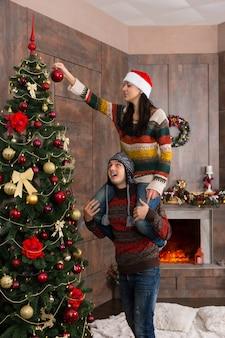 彼女のボーイフレンドの首に座って、装飾された暖炉のあるリビングルームの大きなクリスマスツリーに装飾品や装飾品をぶら下げているかわいい若い女性