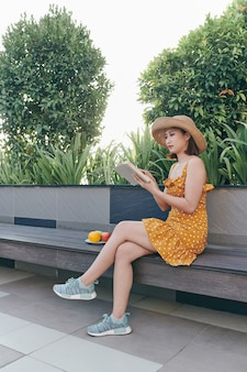 Cute young woman sitting in the park and reading the book