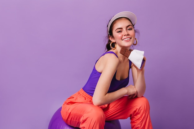 Cute young woman smiling and posing with bar of chocolate on purple wall