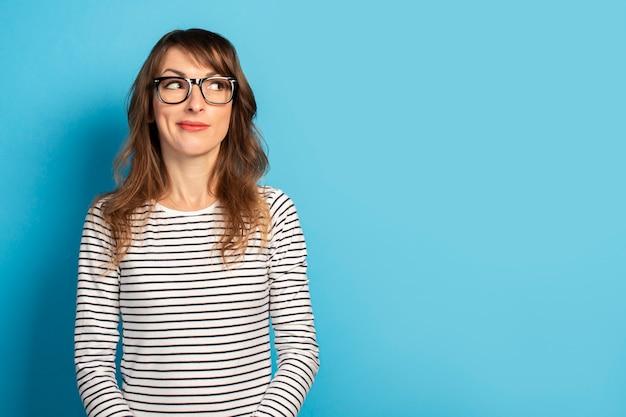 メガネとストライプのセーターを浮かべてかわいい若い女性は青に目をそらします。感情的な顔。コンセプトサプライズ、注意を払う