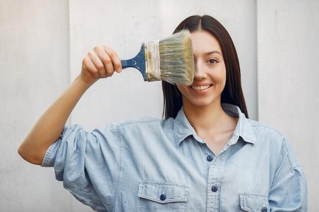 Giovane donna sveglia che sta parete vicina con la spazzola