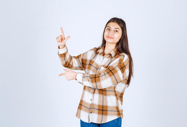 Carina giovane donna in piedi e in posa sul muro bianco.