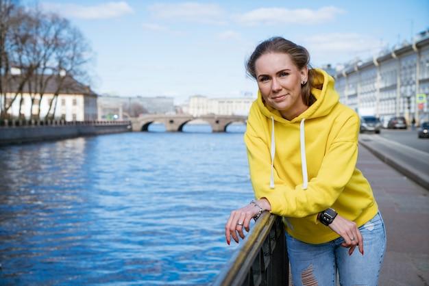 かわいい若い女性は黄色のスウェットシャツの堤防に立っています