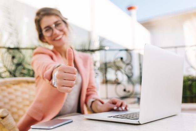 Симпатичная молодая женщина, студент, бизнес-леди показывает палец вверх, молодец, сидя в летнем кафе на террасе с ноутбуком. в розовой шикарной одежде.