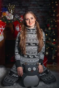Cute young woman in a suit with deer smiles and holds a toy owl against christmas decorations