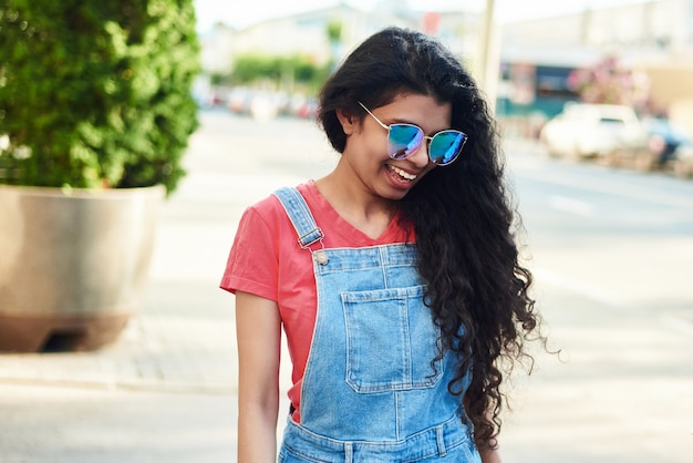 Cute young woman in sunglasses walks along the city street.
