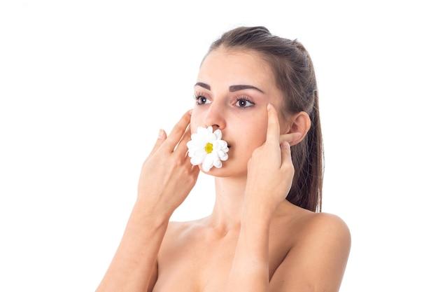 귀여운 젊은 여자는 흰 꽃과 그녀의 피부를 돌합니다