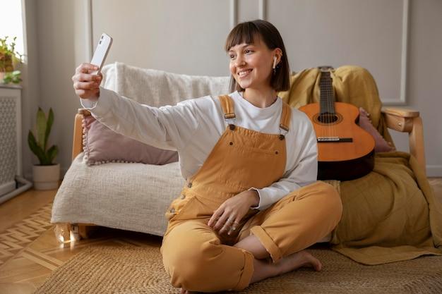 Милая молодая женщина, делающая селфи рядом с ее гитарой