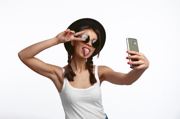 귀여운 젊은 여자 selfie를 복용 하 고 흰 벽에 혀와 평화 제스처를 보여
