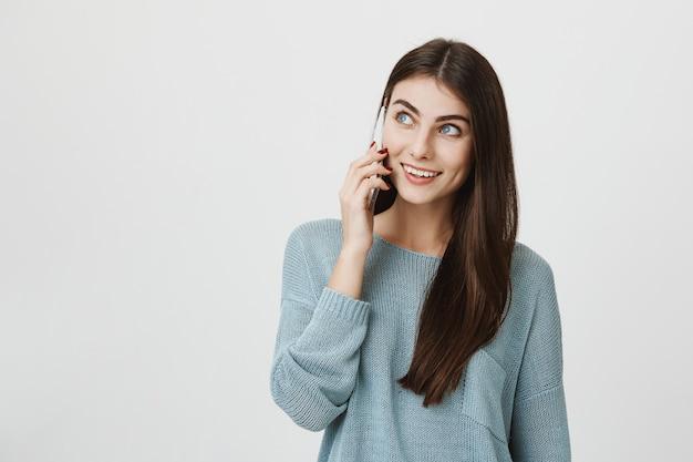 Милая молодая женщина разговаривает по телефону, улыбается и смотрит влево