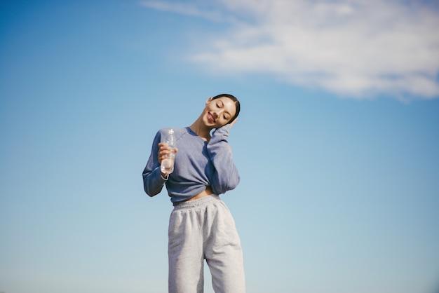 水のボトルとトレーニングかわいい若い女性