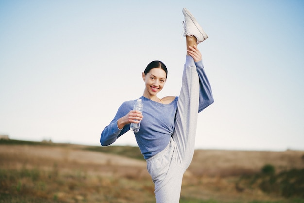 Addestramento sveglio della giovane donna con la bottiglia di acqua