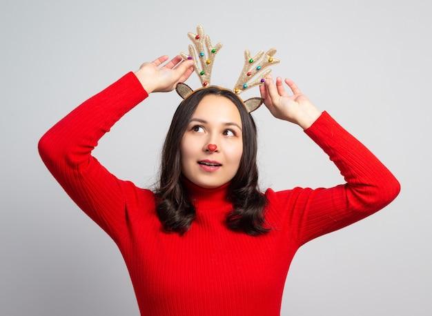 Милая молодая женщина примеряет рога рождественского оленя. на белой поверхности
