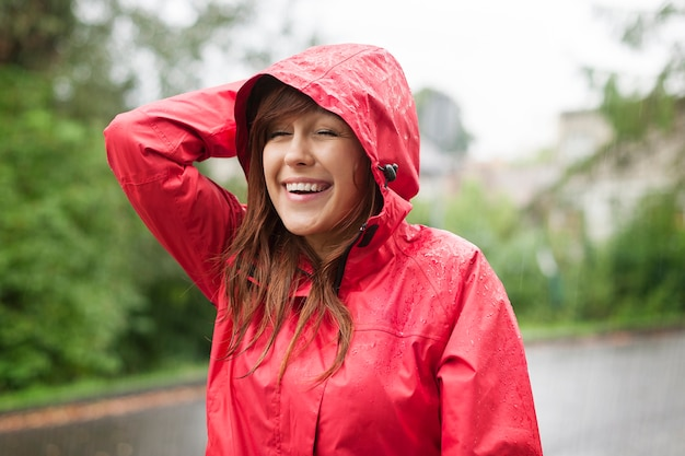 雨の中を歩くかわいい若い女性