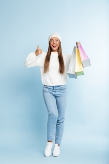 冬の帽子をかぶって、買い物袋を持って保持しているかわいい若い女性。