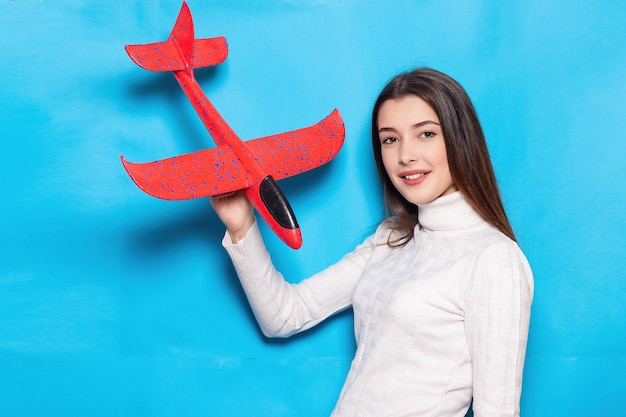 스트라이프 스웨터에 미소와 함께 귀여운 젊은 여자. 그녀의 손에 비행기를 보유 하 고 고립 된 파란색 배경에 그것에 손가락을 가리킵니다. 감정적 인 얼굴입니다. 여행 개념, 항공 비행, 비행기 티켓