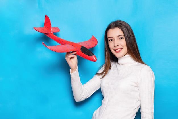 스트라이프 스웨터에 미소를 가진 귀여운 젊은 여자. 그녀의 손에 비행기를 보유하고 격리 된 파란색 배경에 그것에 손가락을 가리 킵니다. 감정적 인 얼굴. 여행 컨셉, 항공 비행, 비행기 티켓