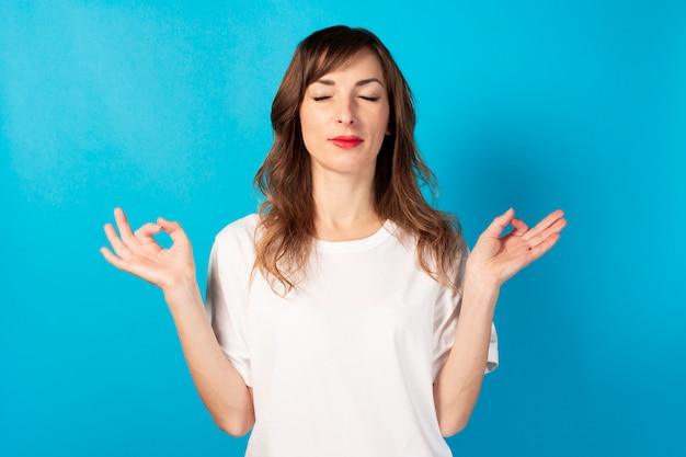 Cute young woman with closed eyes and a white t-shirt makes a gesture with his hands yoga, concentration, meditation on isolated blue. concept of meditation, dreams, planning, good mood
