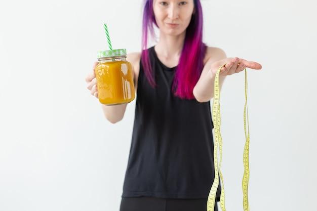 색 머리를 가진 귀여운 젊은 여자는 요가를 시작하기 전에 과일 스무디를 마신다