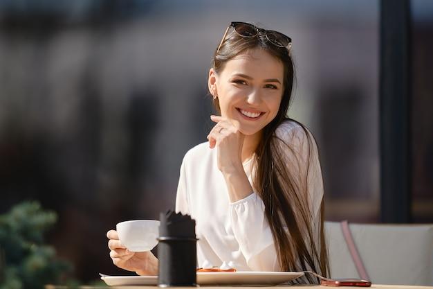 手にカプチーノのカップを持つかわいい若い女性はまっすぐに見え、笑顔