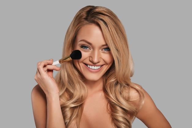 美容製品を適用し、灰色の背景に立って笑っている新鮮な輝く肌を持つかわいい若い女性