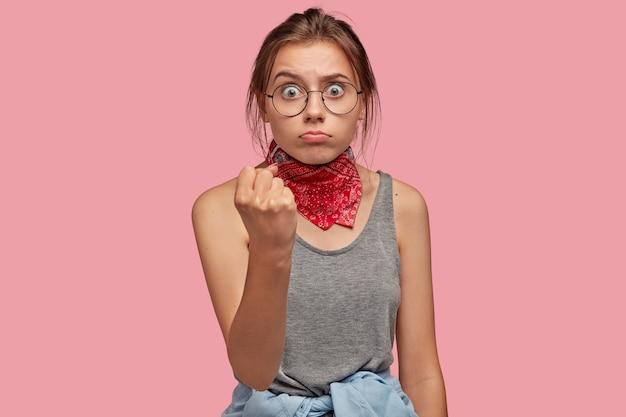 Милая молодая женщина в очках позирует у розовой стены