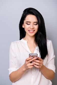 Милая молодая женщина с густыми черными волосами читает смс от своего парня с зубастой улыбкой, стоя на сером пространстве