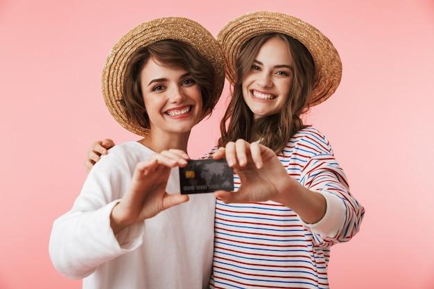 クレジットカードを保持している孤立したポーズでかわいい若い女性の友人。