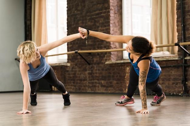 Милые молодые женщины тренируются вместе в тренажерном зале