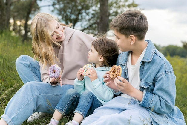 Cute youngsters and mom eating doughnuts