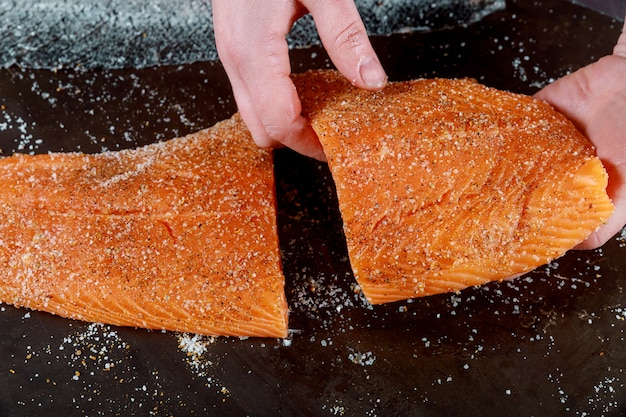 The cuted salmon fillets in hands on black board.