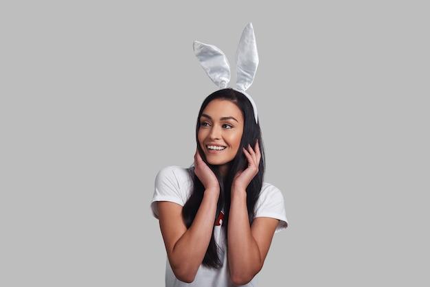 Симпатичнее любого кролика. привлекательная молодая женщина в ушах кролика смотрит в сторону и улыбается, стоя на сером фоне