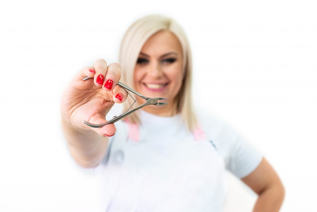 Щипцы для кутикулы. руки держат маникюрный и педикюрный инструмент. копировать пространство. концепция индустрии красоты