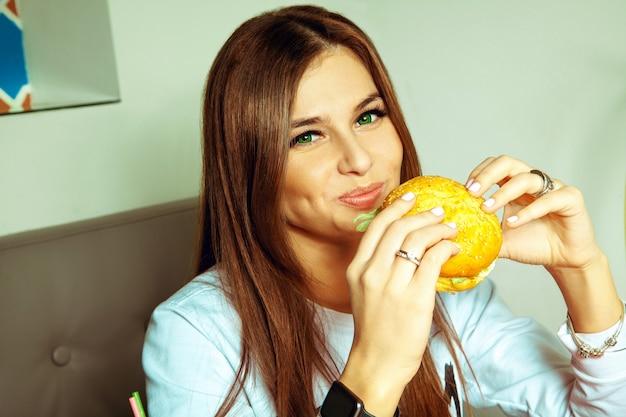 녹색 눈을 가진 큐티 밝은 갈색 머리 소녀는 햄버거를 먹고 정면을보고