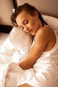 Милая девушка лежит в белой кровати отеля