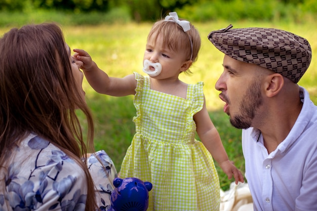 Cutie little baby girl touches her mothers nose at the family picnic at the park