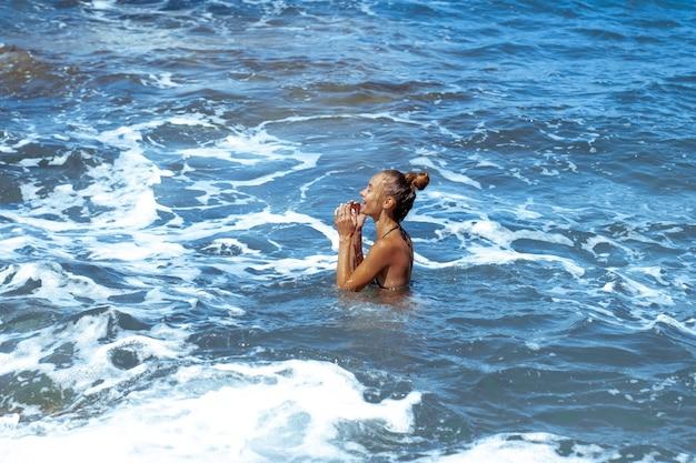 Милашка молодая девушка развлекается в море летом