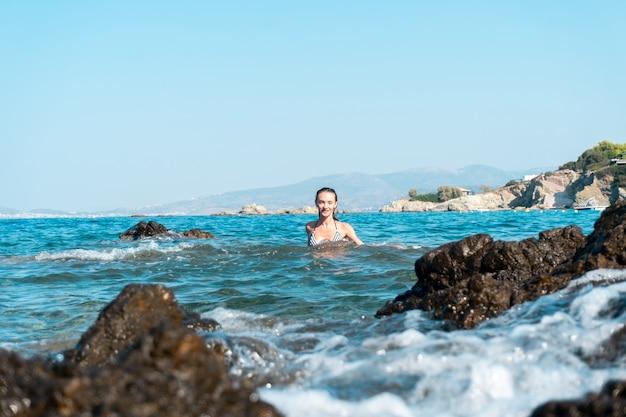 海の夏の時間で楽しんでいるかわい子ちゃんの若い女の子