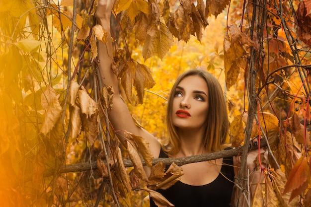 Милая молодая девушка с макияжем позирует в золотом осеннем лесу и смотрит вверх