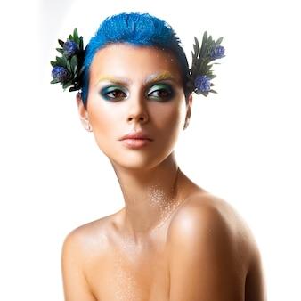 孤立したスタジオショットを離れて見ている髪に多色の化粧と花を持つかわい子ちゃんの若い女の子