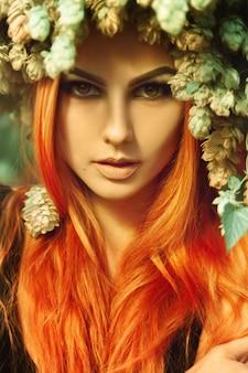 屋外で頭にホップでカメラを見ているキューティーな若い赤毛の女性