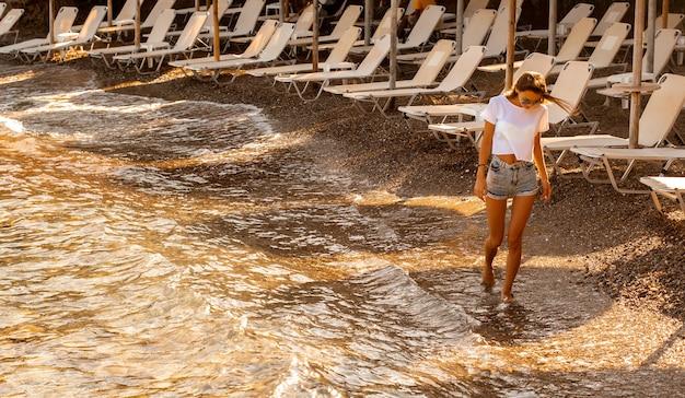 海の夏の時間で楽しんでいるかわい子ちゃんの若い女性
