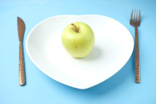 파란색 표면에 녹색 사과와 칼 붙이 및 빈 접시