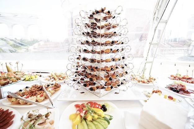 Столовые приборы и различные блюда на раздаточном столе в ресторане